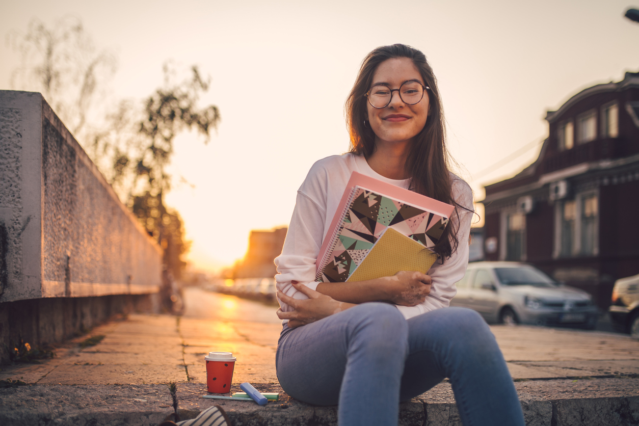 Female student holding books whilst sat on a wall