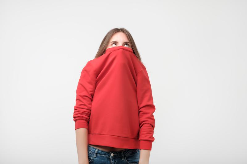 Femme timide se cachant derrière son pull