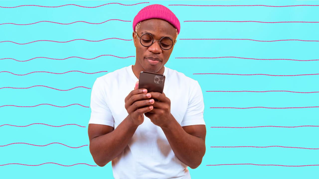 homem de óculos e touca mexendo no celular