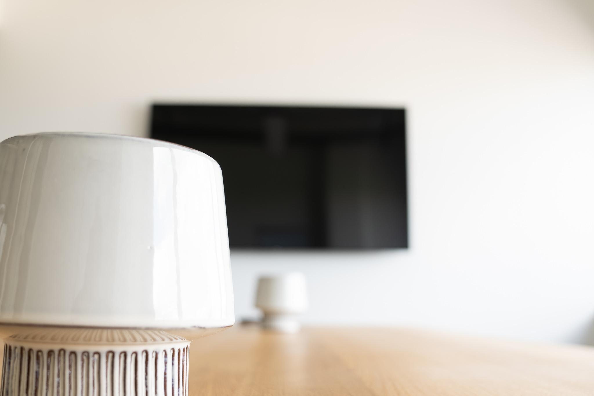 Stehlampe mit einem Bildschirm im Hintergrund