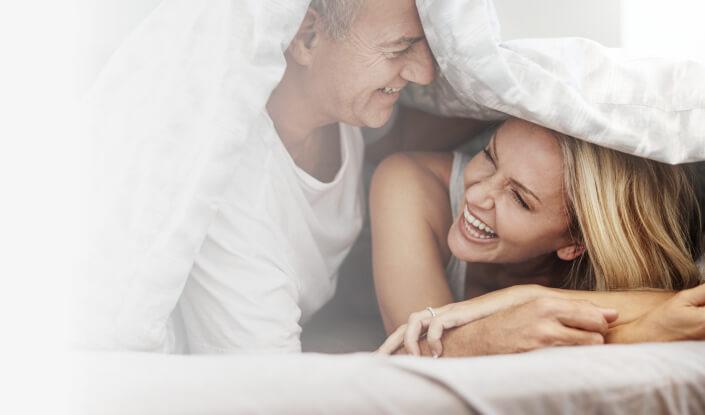 Pärchen lacht zusammen im Bett. | Spring