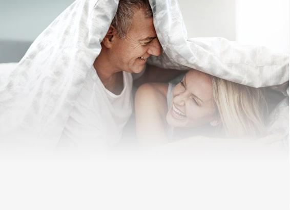 Pärchen lacht zusammen im Bett unter der Decke. | Spring