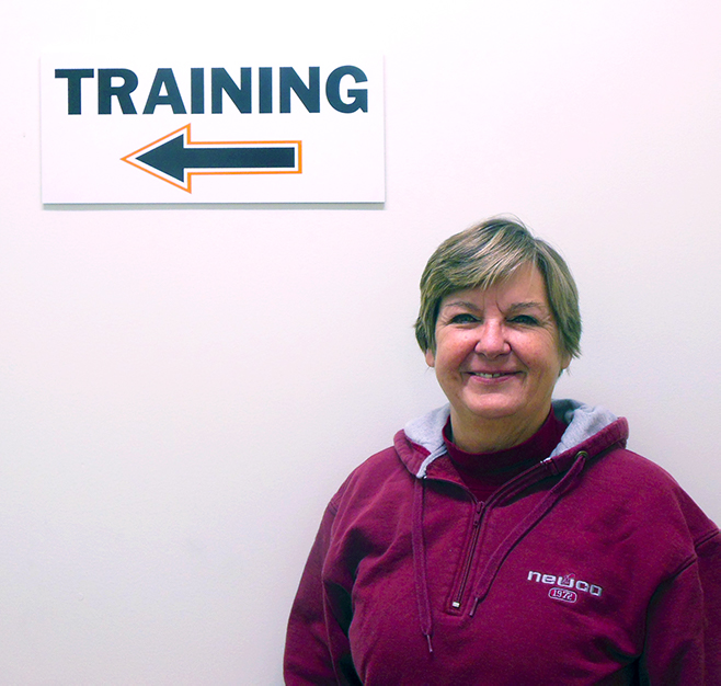 Mary Kinnear standing in front of training sign