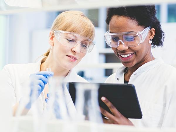Two female scientists looking at a tablet