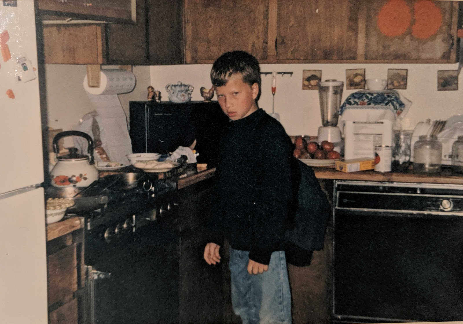 A young Vlad Magdalin stands in a kitchen with a scowl on his face.