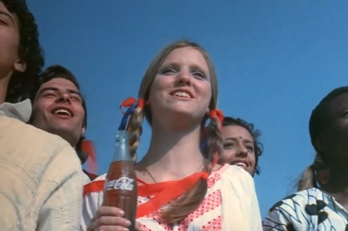 A close up of a woman in a crowd looking happy and holding a bottle of Coca Cola. Circa 1970s.
