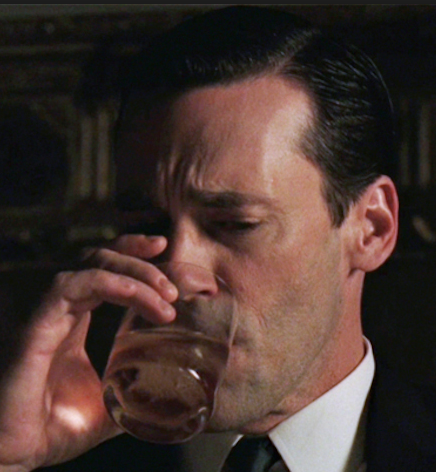 Don Draper drinking alcohol from a glass with a frown on his face.