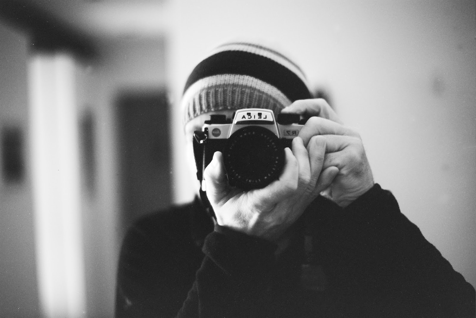 black and white image of person taking a picture with a camera
