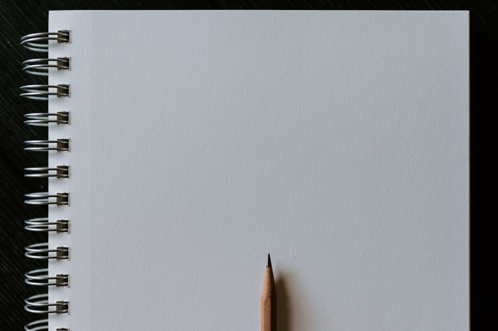 An image of a pencil and notebook.