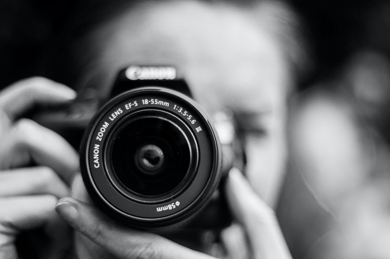 An image of a person taking a picture with a Canon camera.