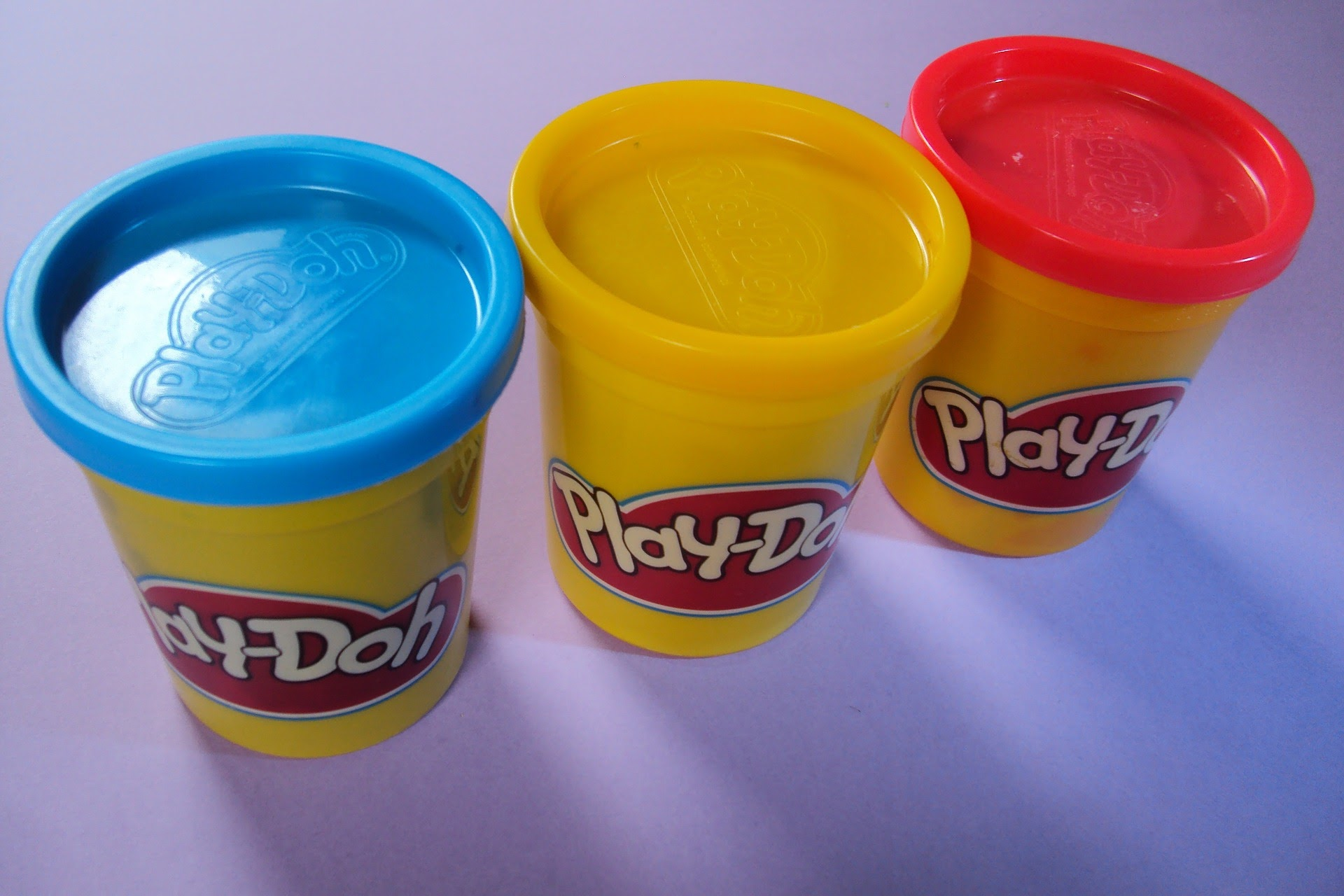 An image of blue, yellow, and red Play-Doh containers.