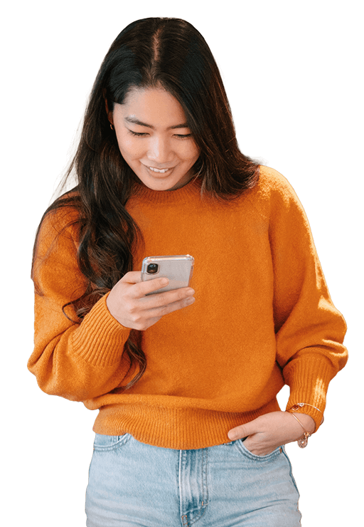 Japanese woman in orange sweater, smiling on her phone