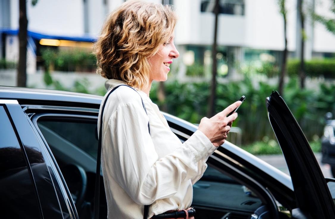 Mujer leyendo un mensaje al lado de su coche