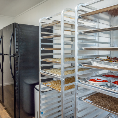tall drying racks and a modern refrigerator stand at the ready in a seed bank built inside a durable steel shipping container. The seed bank facility is one of the first of its kind made by Terraformation and can be used to process and store tens of thousands of seeds a year