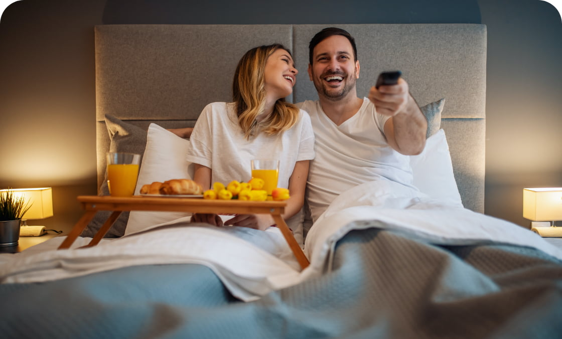 Couple enjoying entertainment on Astro TV while in a hotel room while eating breakfast