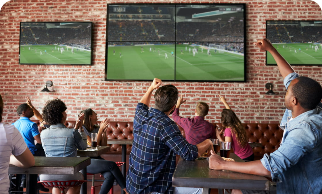 Crowd at a bar or restaurant having fun cheering during a football match on Astro TV