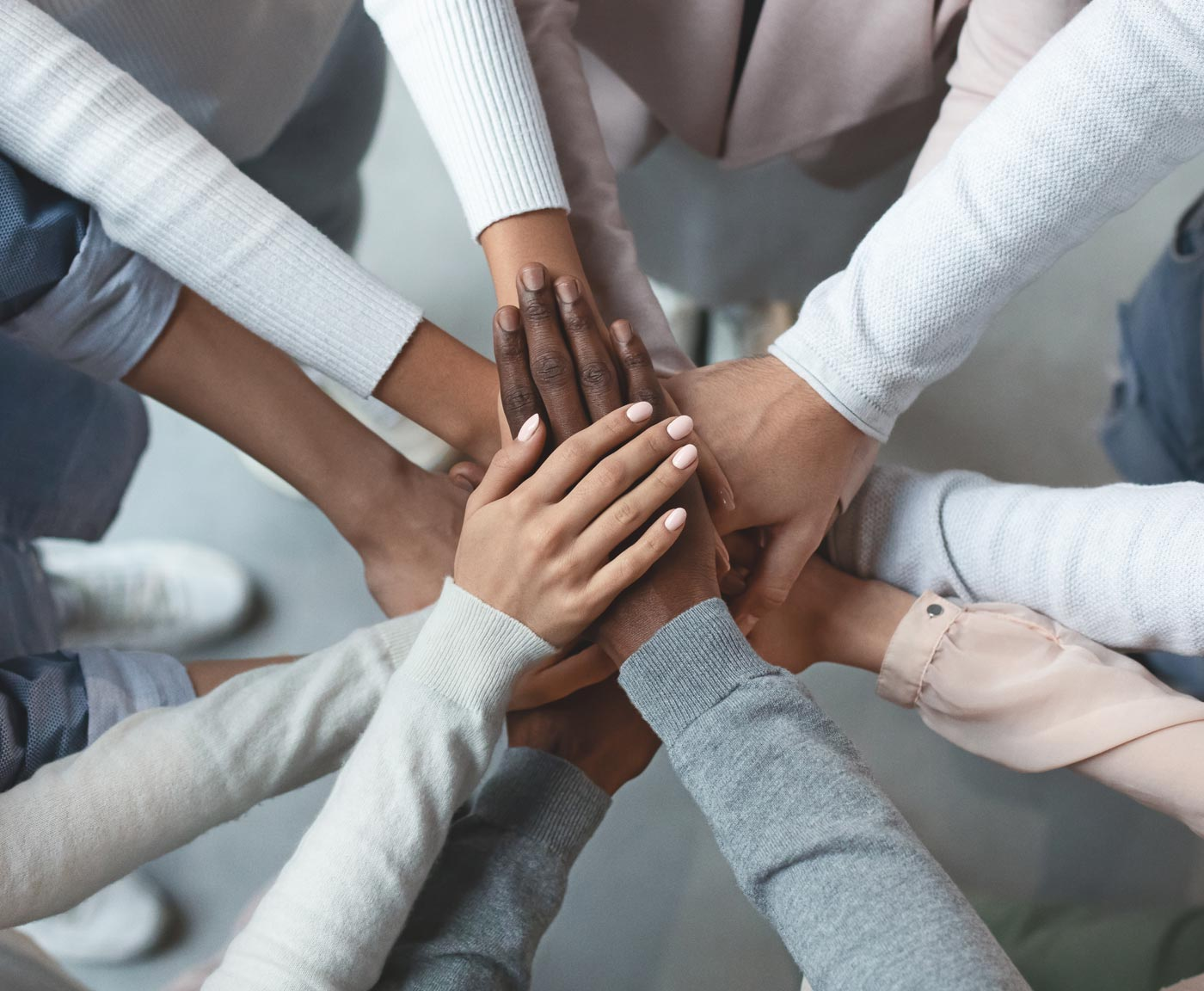 A close up of a team showing unity with putting their hands together on top of each other