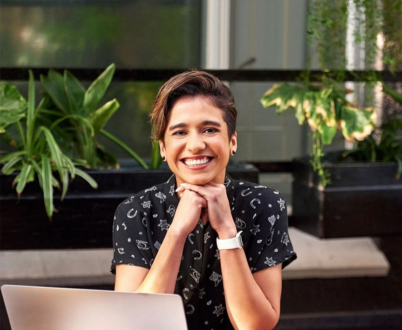 A smiling woman sat at a laptop computer