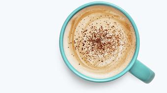A teal mug of coffee with chocolate sprinkles
