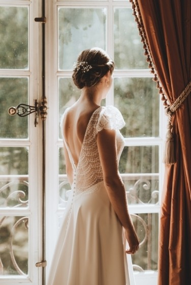 La mariée devant la fenêtre avec sa robe