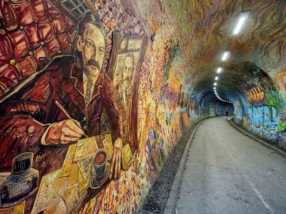 A colourful mural covering the whole tunnel with Robert Louise Stevenson in the foreground
