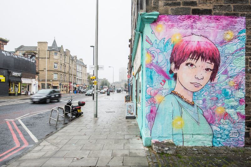 On the corner of a building, this mural shows a bright image of a person with purple hairo