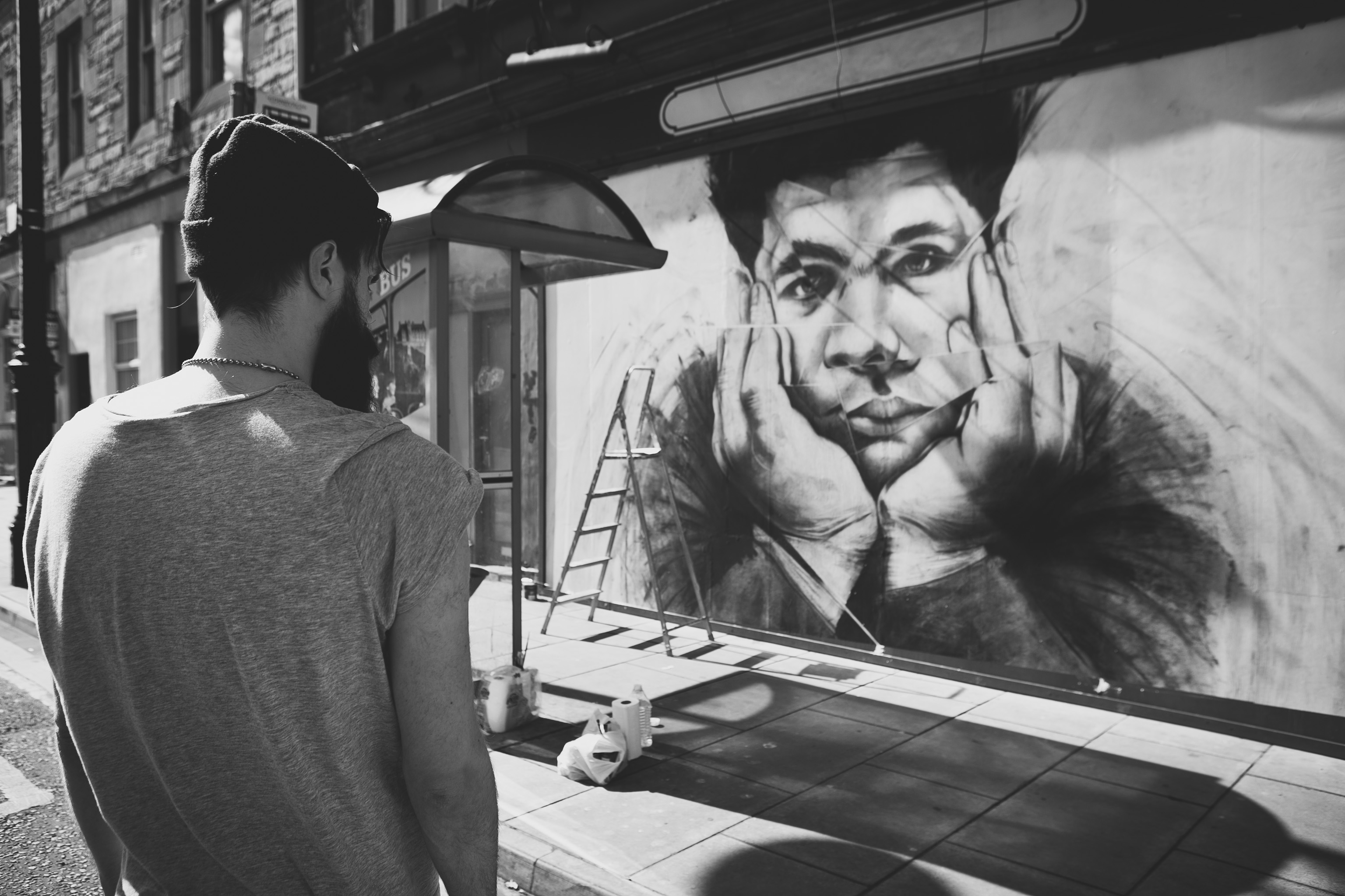 A man looks onto the mural showing a boy with his face in his hands