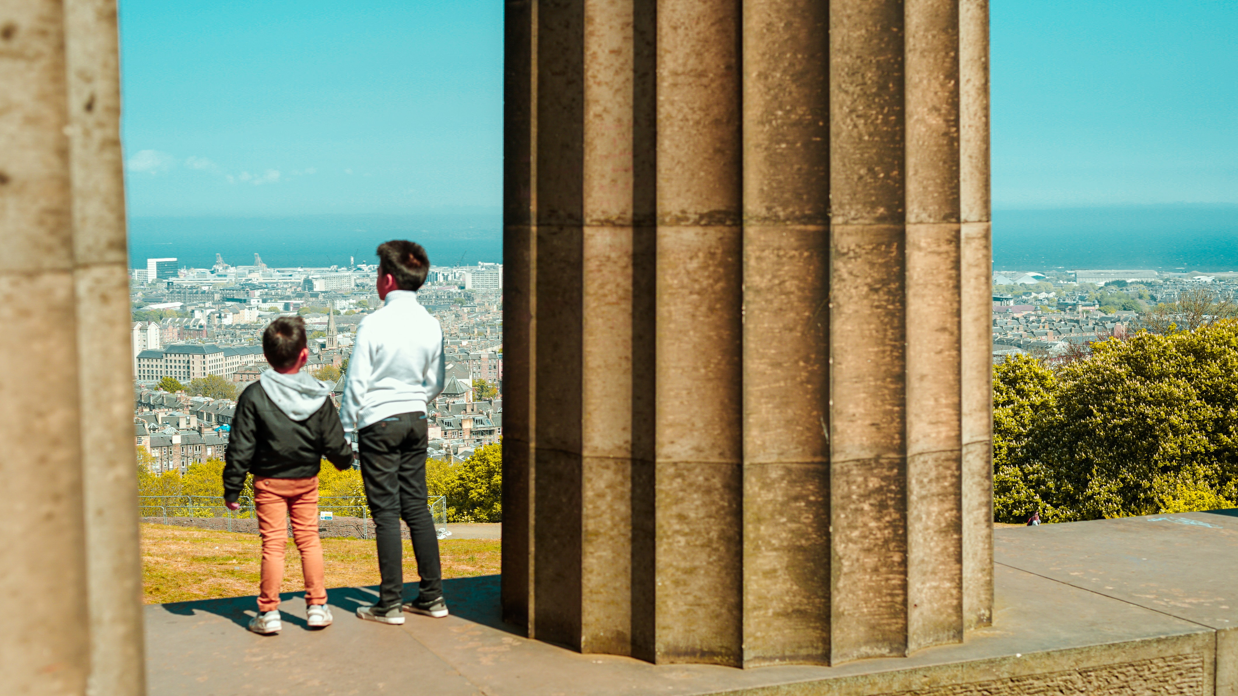 Two children stand with their backs facing the camera on the National Monument of Scotland with views of Edinburgh in front of them