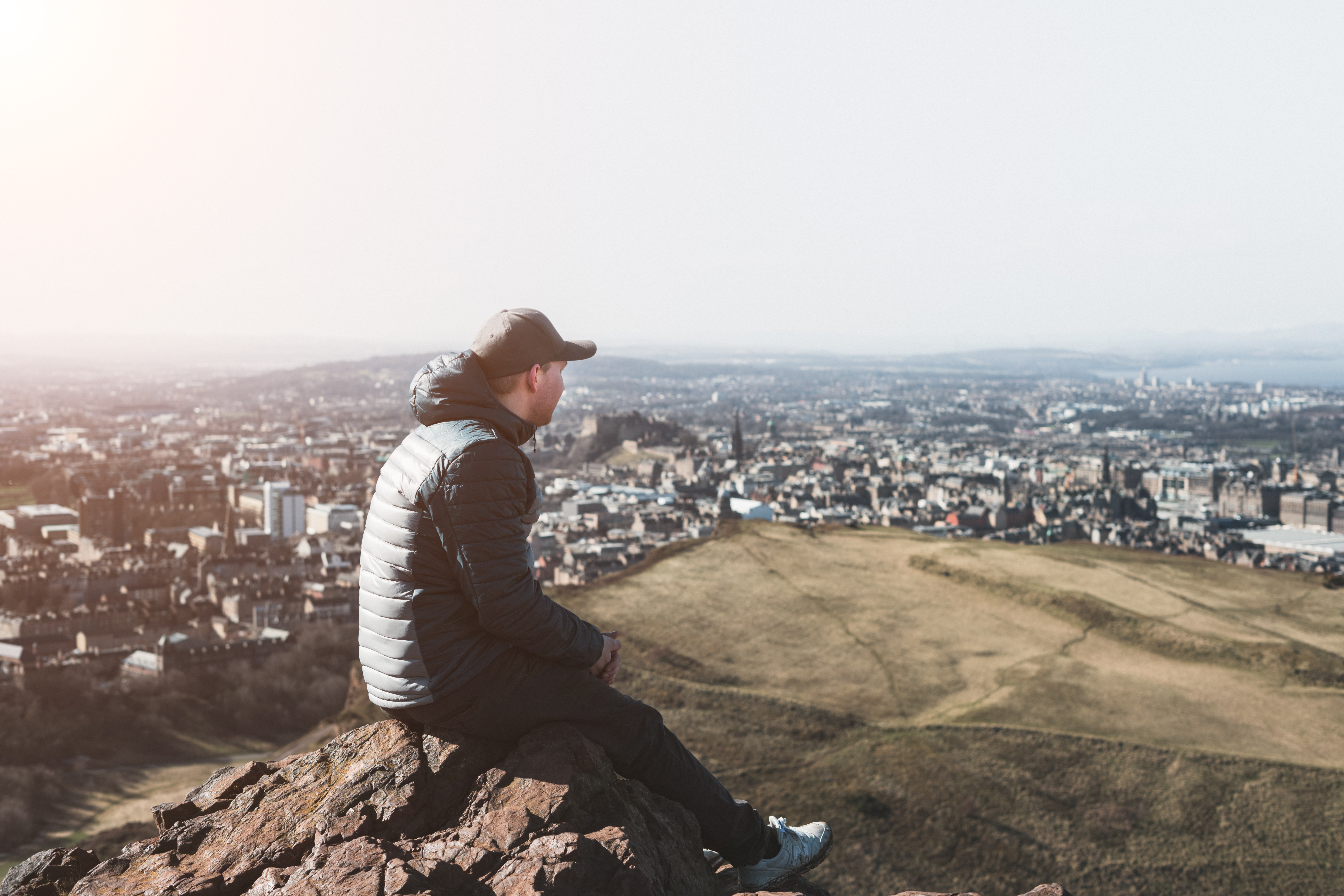 A man sits on top of Arthur's Seat looking out onto views of Edinburgh