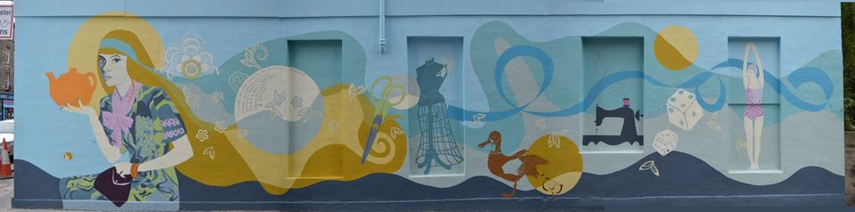 The blue and yellow mural shows a woman, a sewing machine and a bird