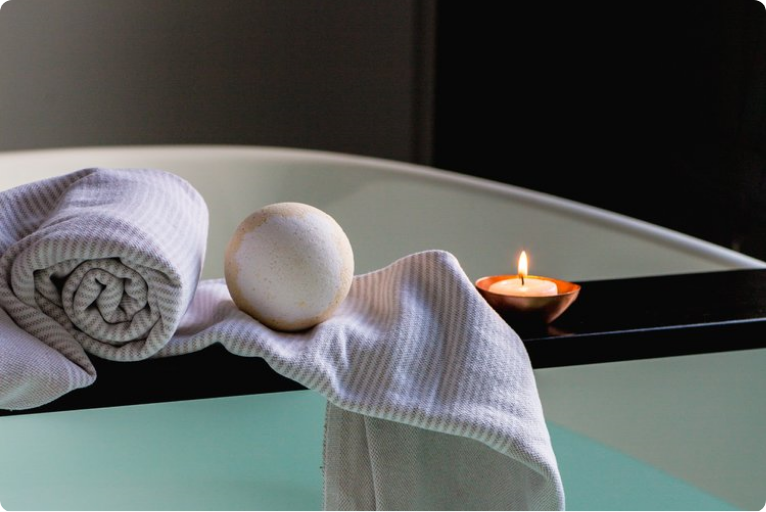 bath bomb, towel, and candle positioned for a relaxing soak