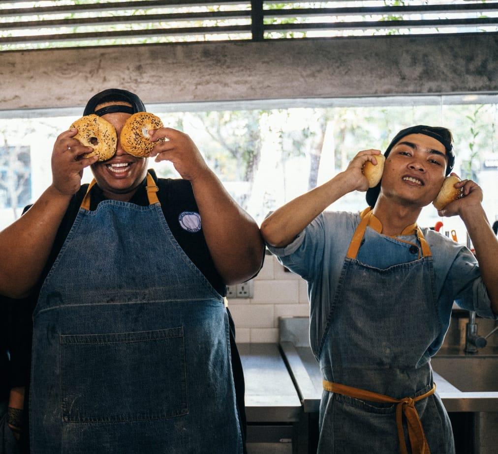 Employees having fun holding bagels up to their eyes