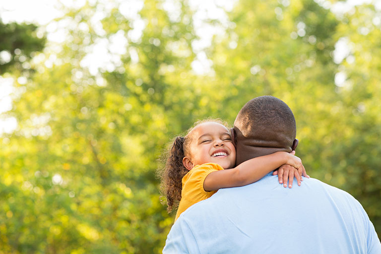 A young smiling Black girl hugging her father. Trees in the background.