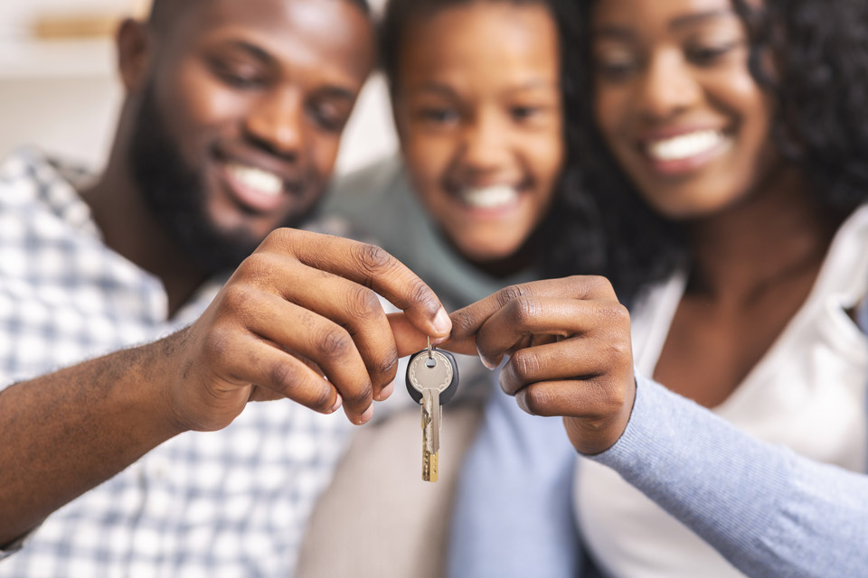 Happy couple with child holding up the keys to their new home