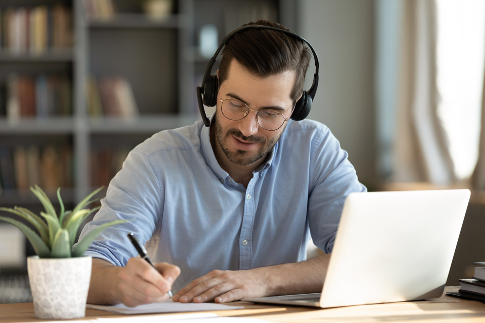 Person wearing headphones writing in notebook in home office