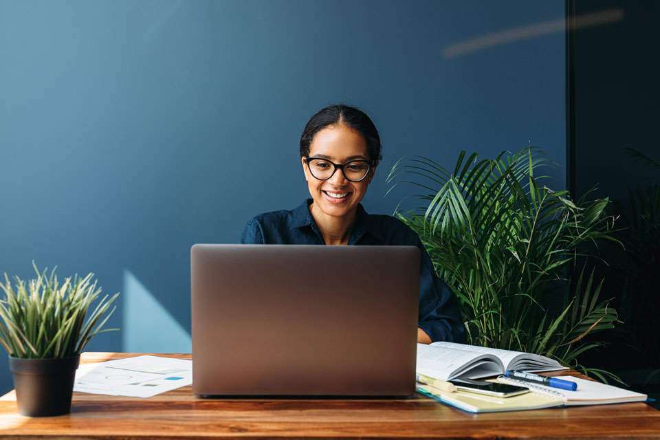 Professional person in glasses working in blue home office space with potted plants