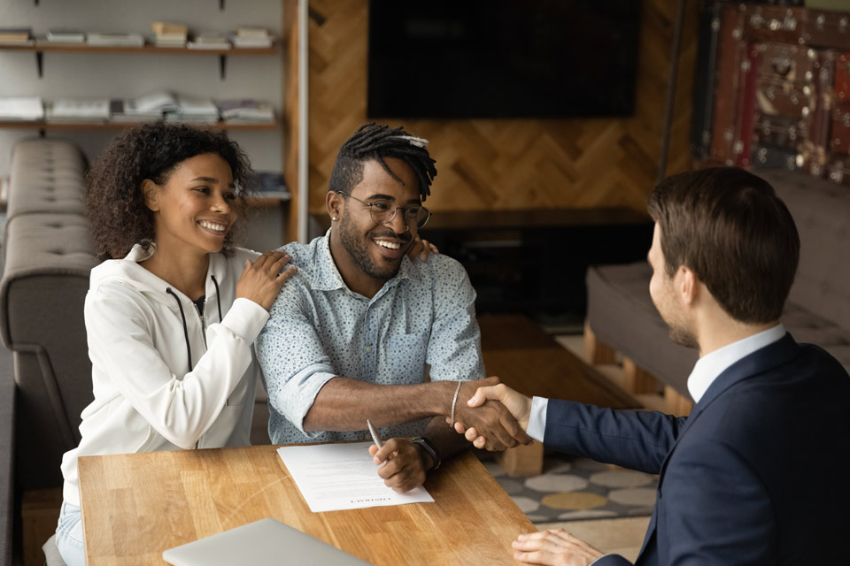 Young couple shaking hands with professional-looking man in suit in an office