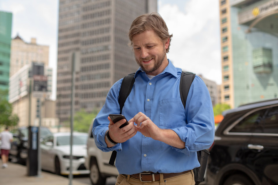 Appraiser looking at smart phone in downtown Detroit