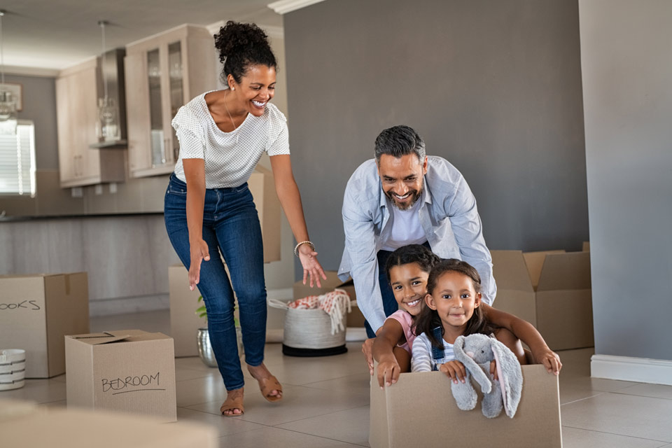 Happy mother and father sliding two kids around in moving box