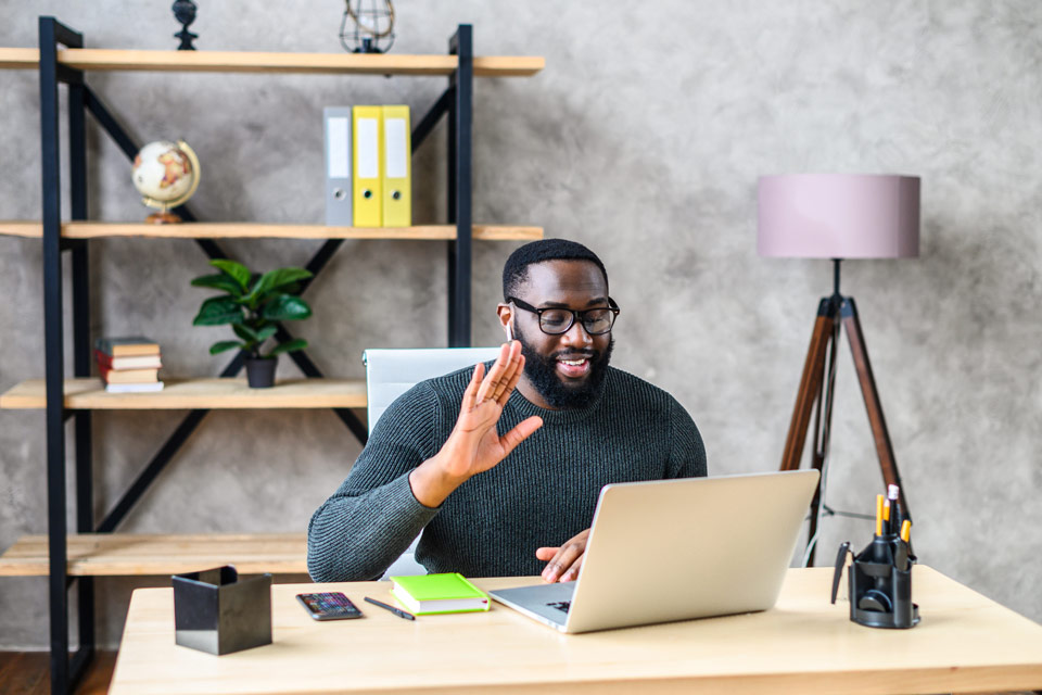 Man in office using laptop for video call