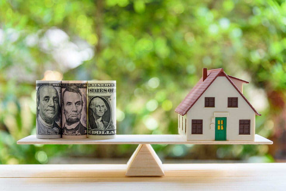 miniature house and money balanced evenly on scale