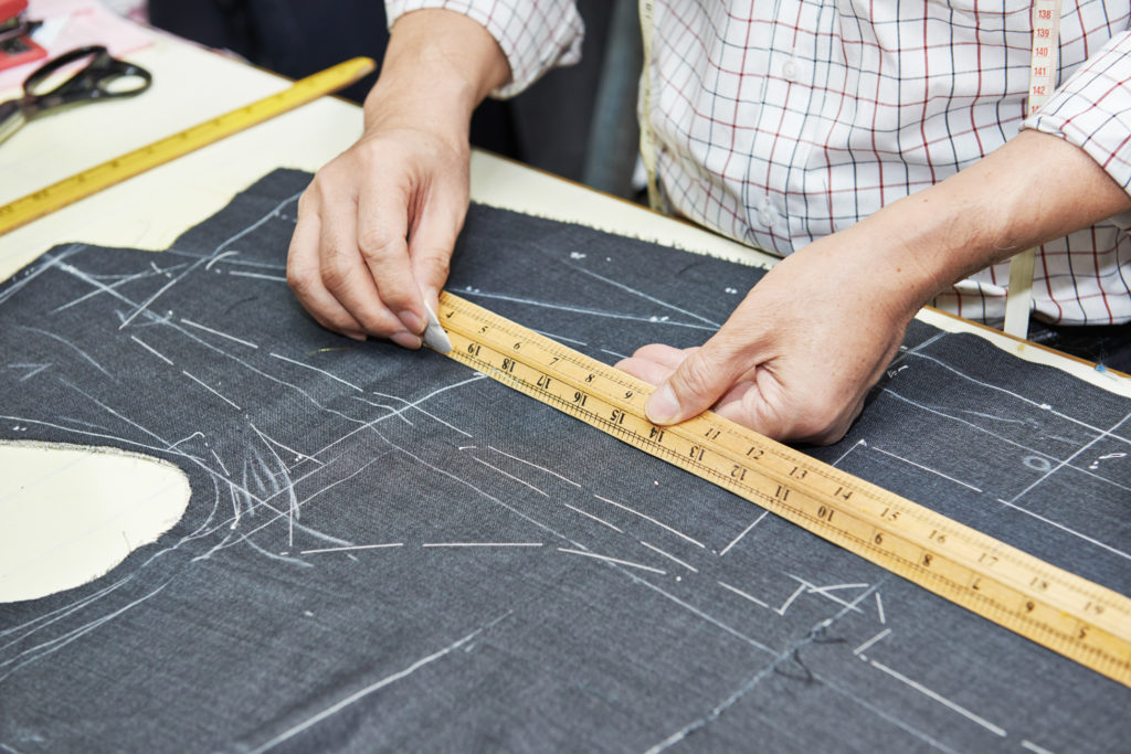 An image of a tailor measuring fabric, indicative of tailoring energy tariff choice to save energy and money