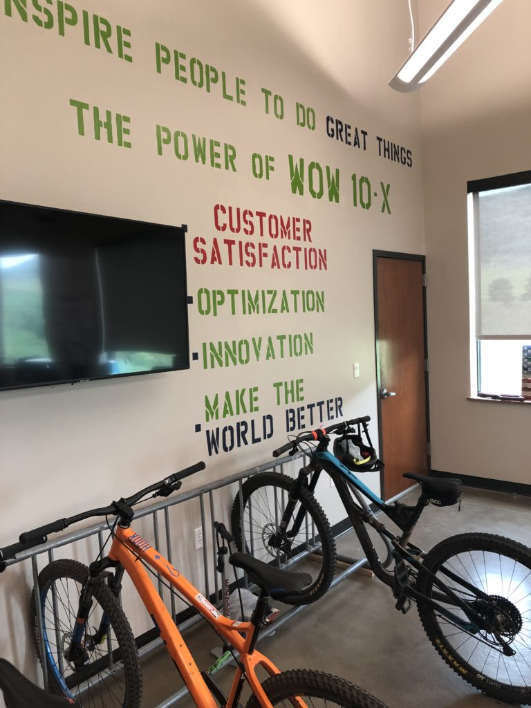 """Photo of interior of Emporia Energy offices in Littleton, CO where a wall lists the company's central pillars, one of which is to """"make the world better"""""""