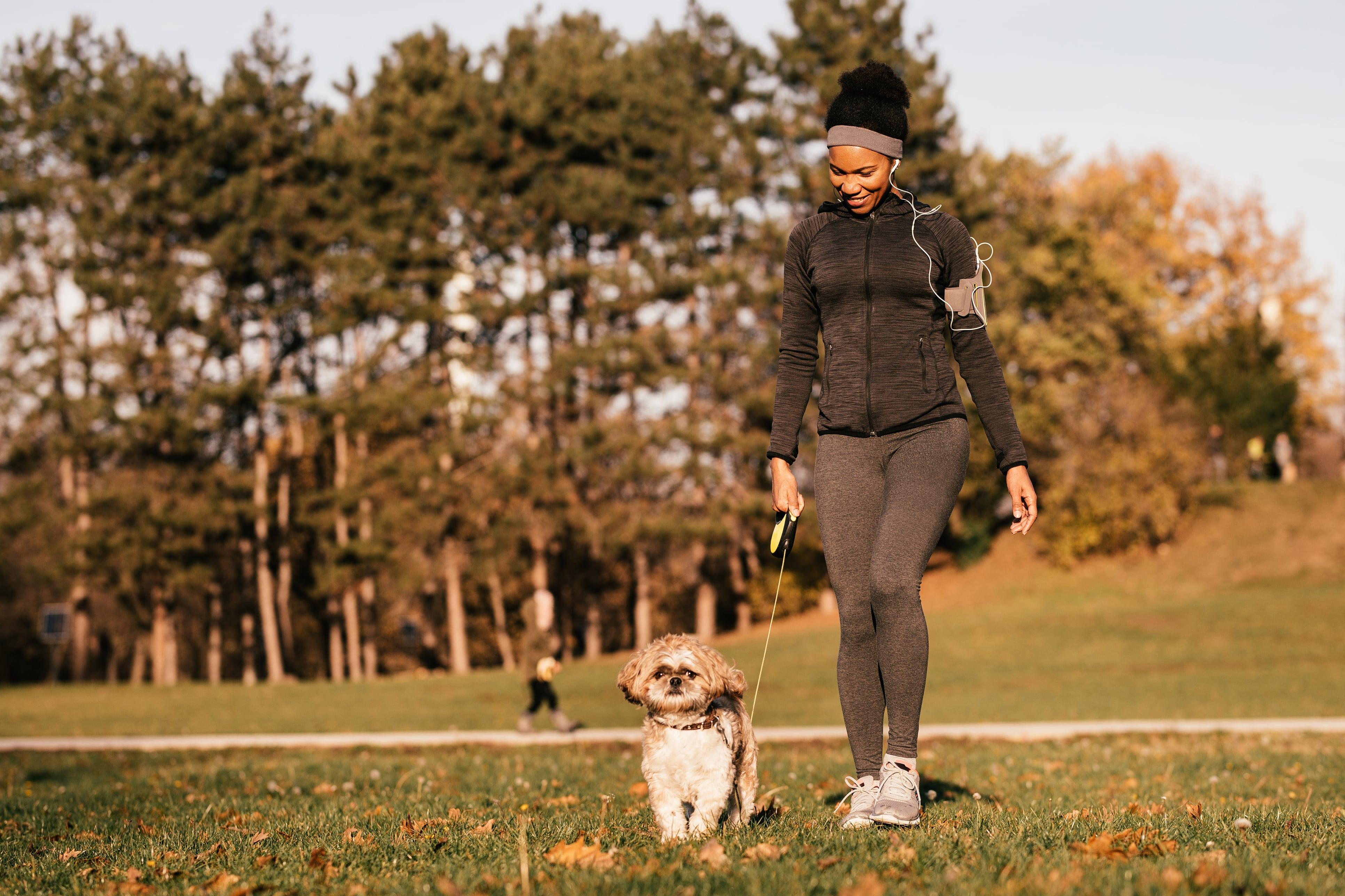 Woman in jogging gear walking a dog