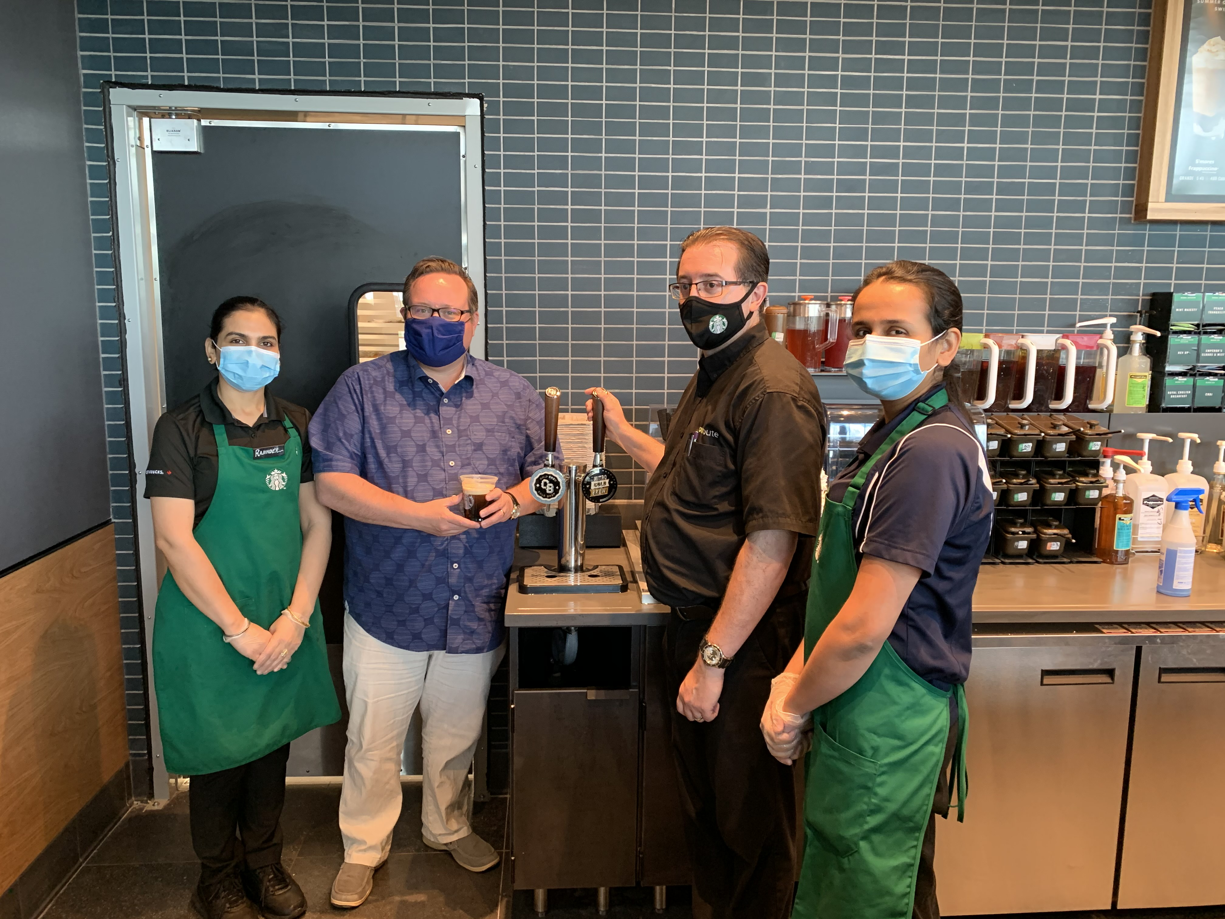 """Employees by a """"Cold Brew"""" tap"""