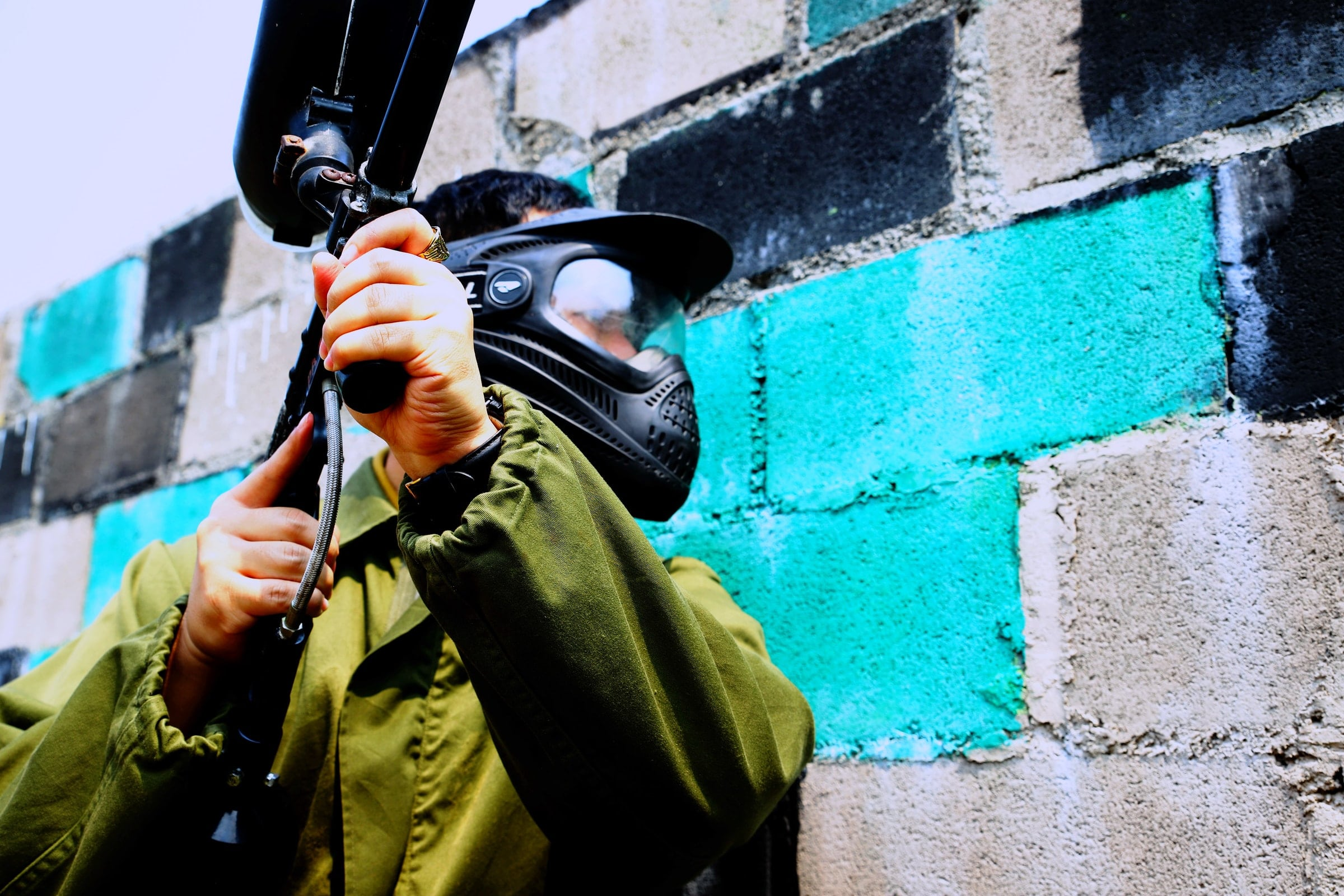 Person wearing paintball mask and holding paintball gun