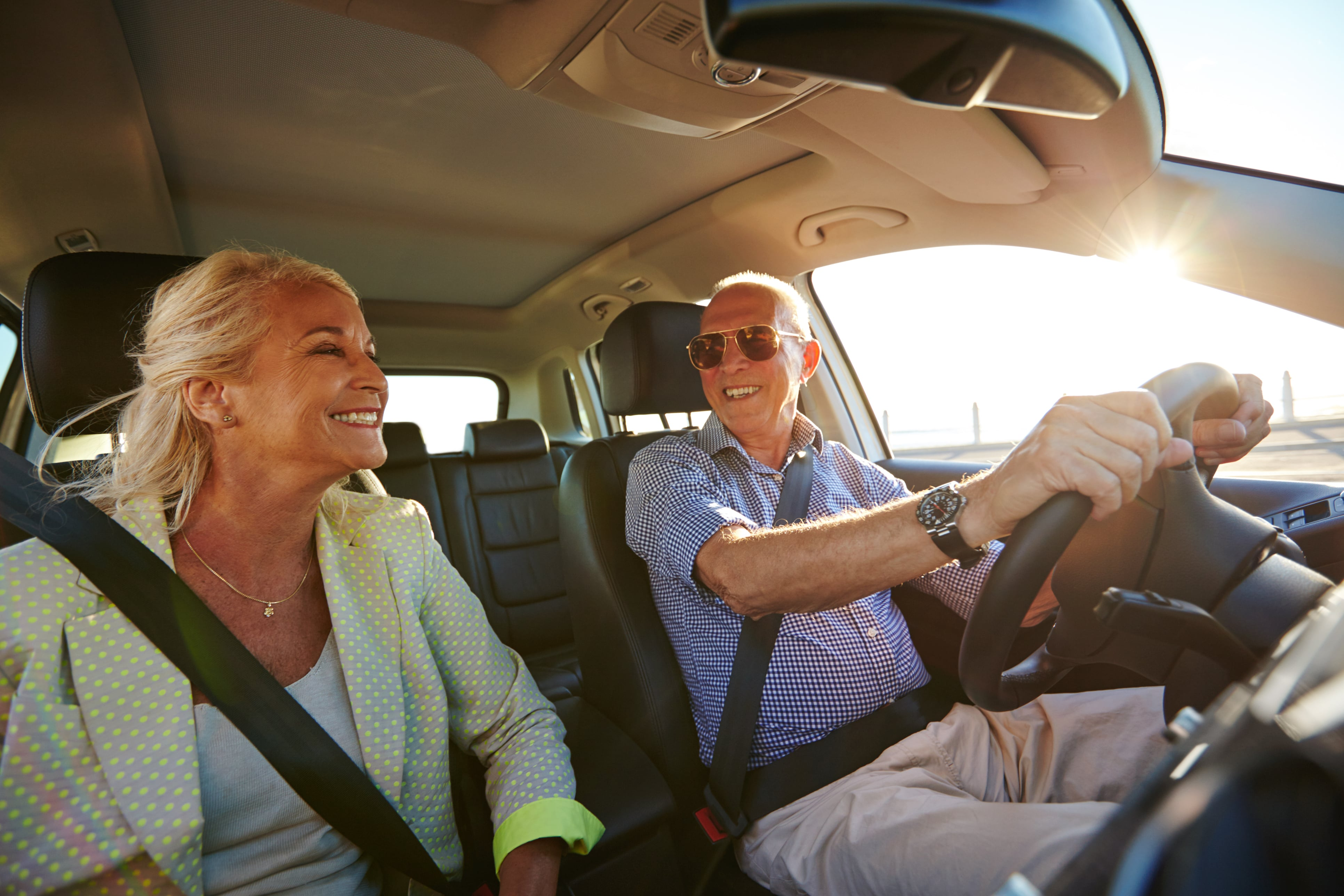 Senior couple driving in a car on a sunny day