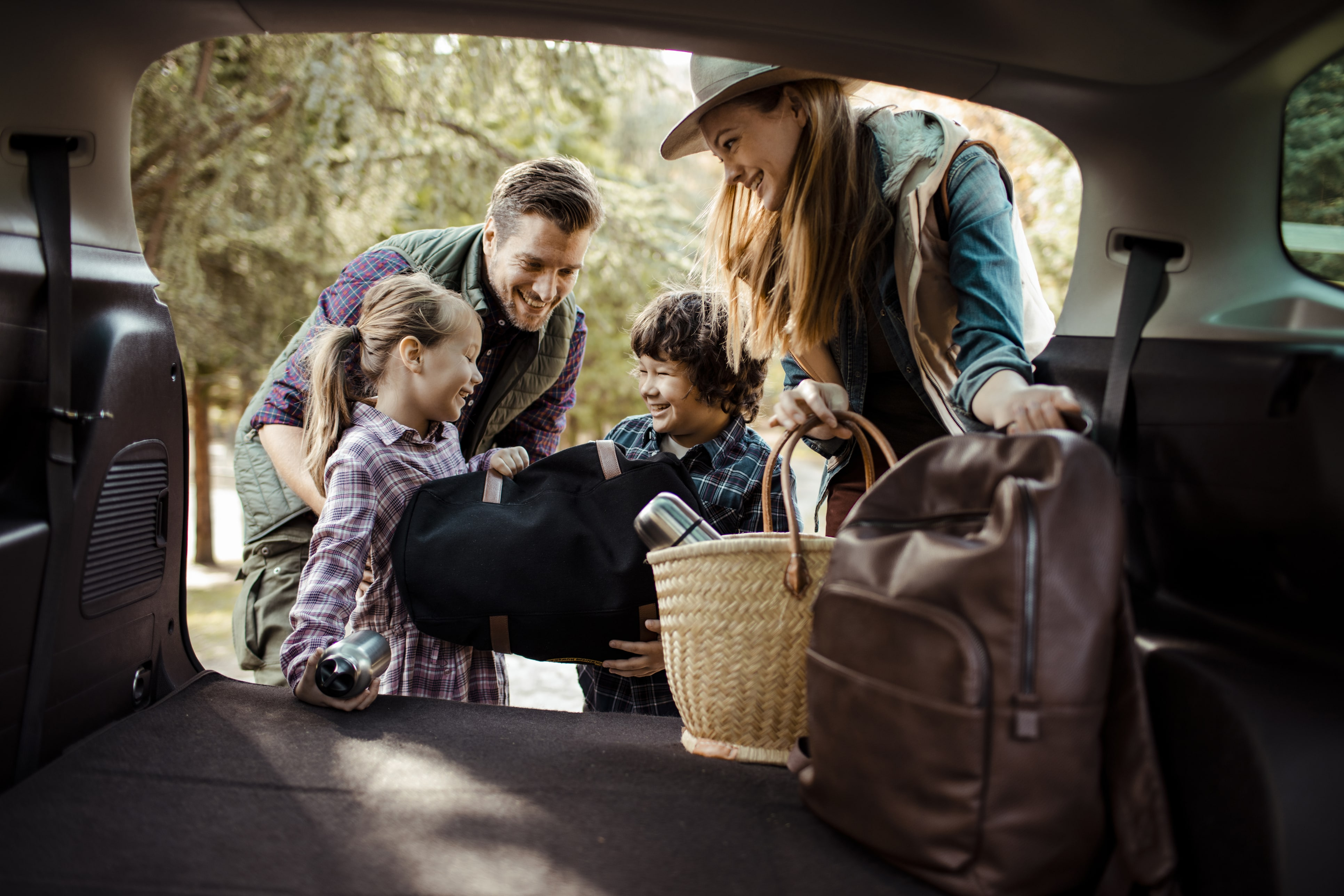 Young family putting bags in trunk of car