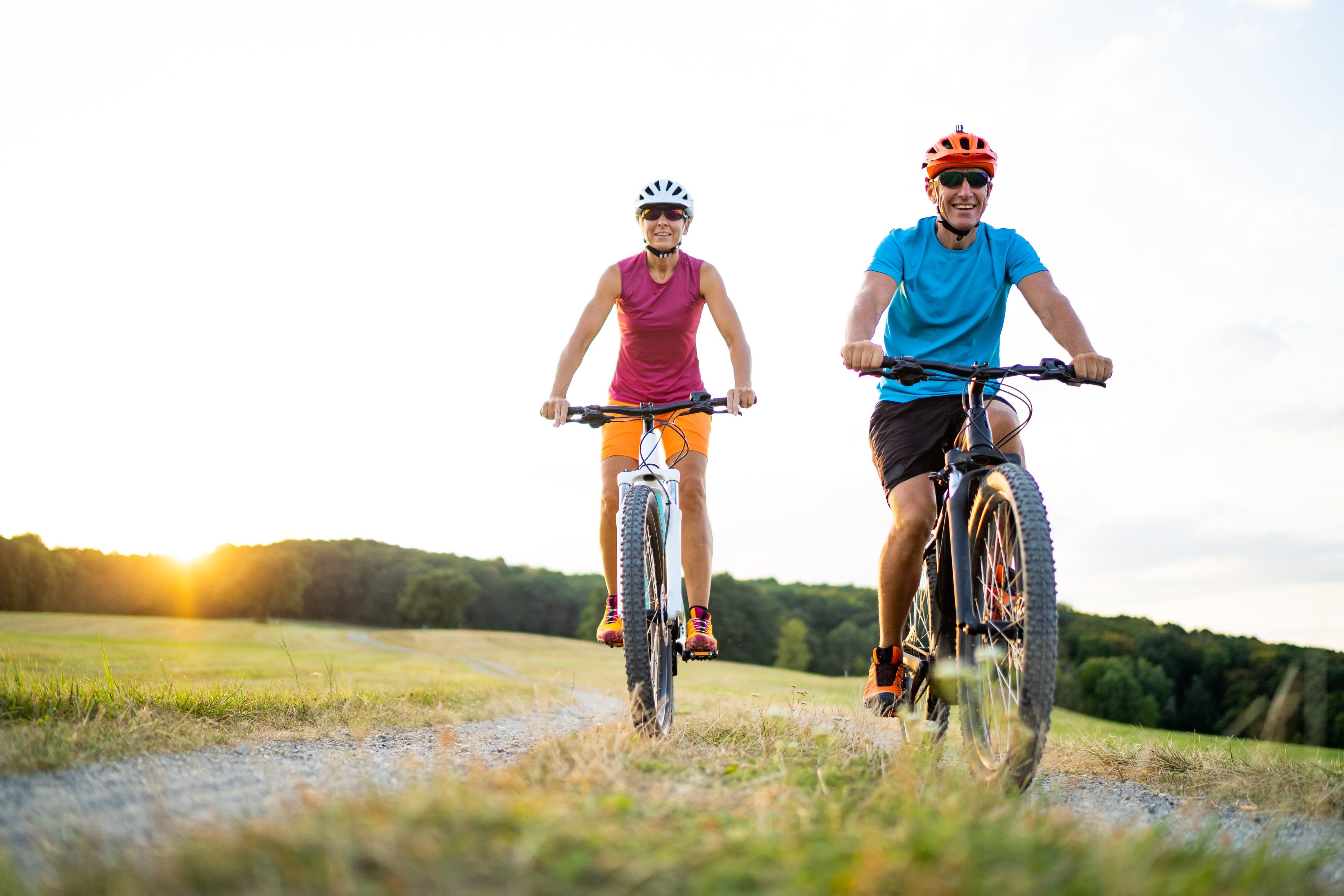 Senior couple cycling through a field