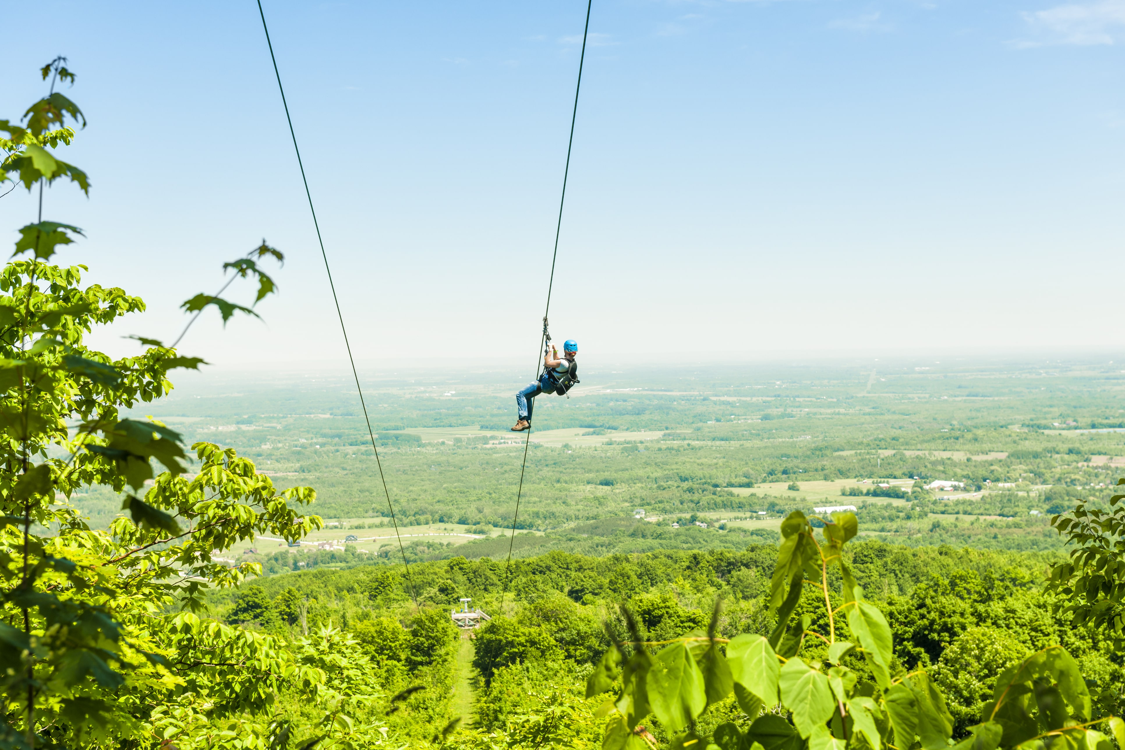 Person zip-lining through valley